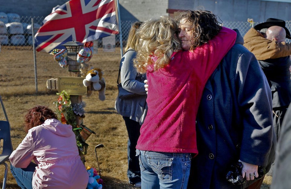 Photo - Danni Legg receives a hug as they stands next to her son's, Christopher, wooden cross that is outside the Plaza Towers Elementary School during a balloon release to mark what would have been Christopher's tenth birthday in Moore, Okla. on Thursday, Jan. 16, 2014. Christopher was killed along with six others when the May 20th tornado hit the school. Parents of those killed have been notified that the crosses will need to be removed for further rebuilding of the school. Photo by Chris Landsberger, The Oklahoman
