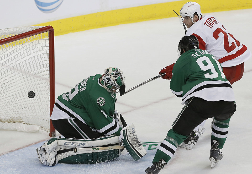 Photo - Dallas Stars goalie Kari Lehtonen (32) and forward Tyler Seguin (91) are unable to stop Detroit Red Wings forward Tomas Tatar (21) from scoring a goal in the second period of an NHL hockey game, Saturday, Jan. 4, 2014, in Dallas. (AP Photo/Brandon Wade)