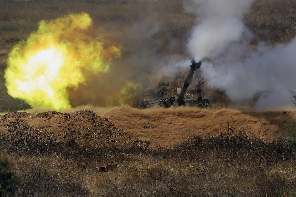 Photo - Israeli artillery fires towards Gaza, near the Israel and Gaza border in the morning of Sunday, July 27, 2014. Hamas on Sunday agreed to observe a 24-hour truce in Gaza after initially rejecting a similar Israeli offer, as fighting resumed and the two sides wrangled over the terms of a lull that international diplomats had hoped could be expanded into a more sustainable truce. Hamas spokesman Sami Abu Zuhri said the truce would go into effect at 2 p.m. (1100 GMT) Sunday. But shortly after the truce was to have started warning sirens wailed in southern Israel and the military said three rockets landed in the area, without causing casualties or damage. (AP Photo/Tsafrir Abayov)