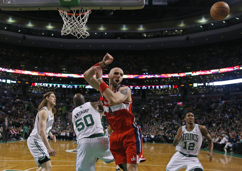 Photo - The ball gets away from Washington Wizards center Marcin Gortat (4) after he crashed into Boston Celtics center Joel Anthony (50) as Celtics center Kelly Olynyk (41) and forward Chris Johnson (12) look on during the second half of an NBA basketball game in Boston, Wednesday, April 16, 2014. The Wizards won 118-102. (AP Photo/Elise Amendola)