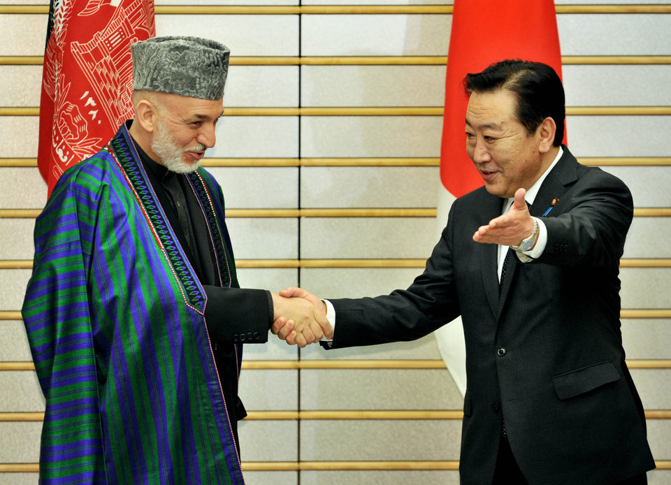 Photo -   Afghan President Hamid Karzai, left, is greeted by Japanese Prime Minister Yoshihiko Noda for their talks at Noda's office in Tokyo Monday, July 9, 2012. Karzai said Monday he is encouraged by pledges to provide Afghanistan with $16 billion in aid, but warned that corruption in his country cannot be rooted out unless donors themselves take more action. (AP Photo/Yoshikazu Tsuno, Pool)