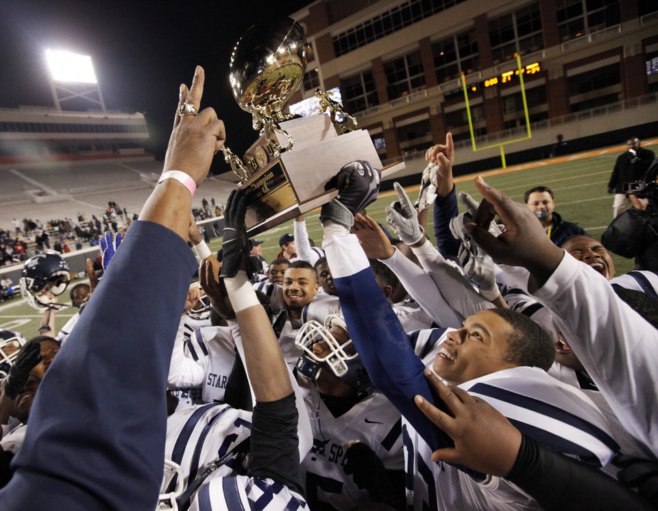Photo - The Star Spencer Bobcats celebrate with the championship trophy after the Class 4A high school football state championship game between Star Spencer and Douglass at Boone Pickens Stadium in Stillwater, Okla., Saturday, December 5, 2009. Star Spencer won, 34-21. Photo by Nate Billings, The Oklahoman