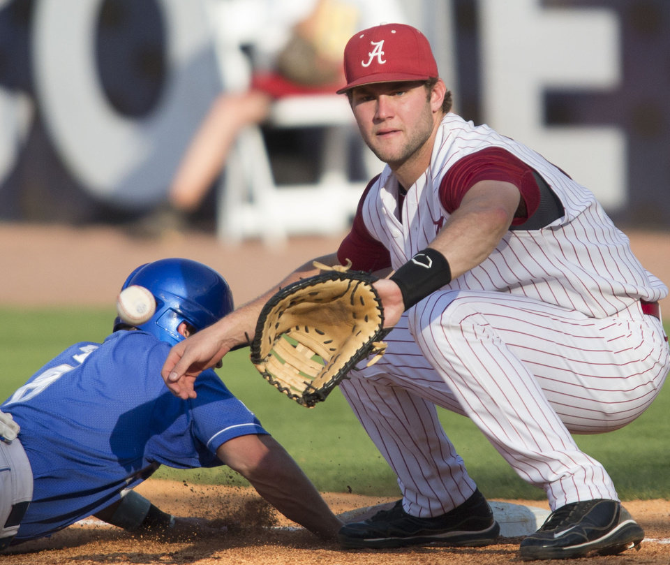 Photo - Alabama's Austen Smith can't get the ball in time to tag Kentucky's Matt Reida  at first on a pick off play during the Southeastern Conference NCAA college baseball tournament on Tuesday, May 20, 2014, in Hoover, Ala. (AP Photo/Hal Yeager)