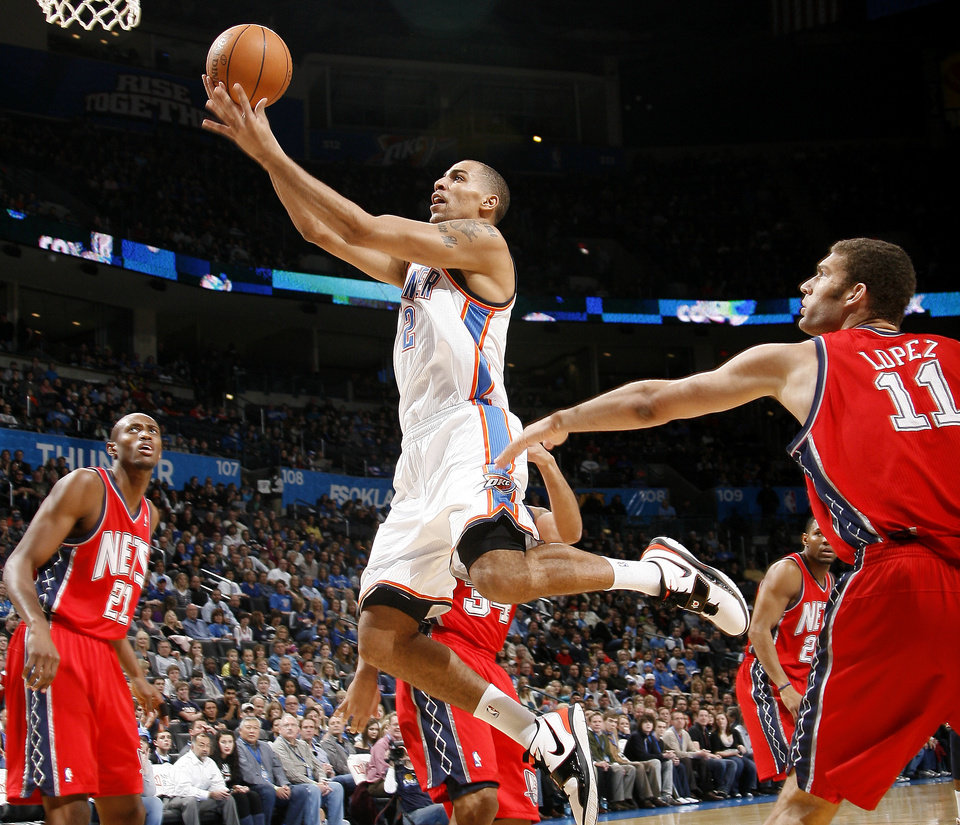 Photo - Oklahoma City's Thabo Sefolosha goes to the basket between New Jersey's Travis Outlaw, left, and Brook Lopez during the NBA basketball game between the Oklahoma City Thunder and the New Jersey Nets at the Oklahoma City Arena, Wednesday, Dec. 29, 2010.  Photo by Bryan Terry, The Oklahoman