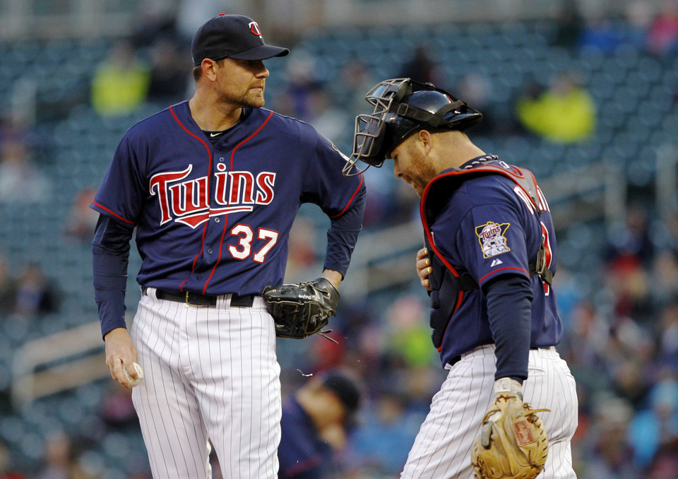 Minnesota Twins starting pitcher Mike Pelfrey (37) and catcher Ryan Doumit, right, react after Miami Marlins catcher Rob Brantly hit a two-run double during the first inning in the second baseball game of a doubleheader Tuesday, April 23, 2013, in Minneapolis. (AP Photo/Genevieve Ross)