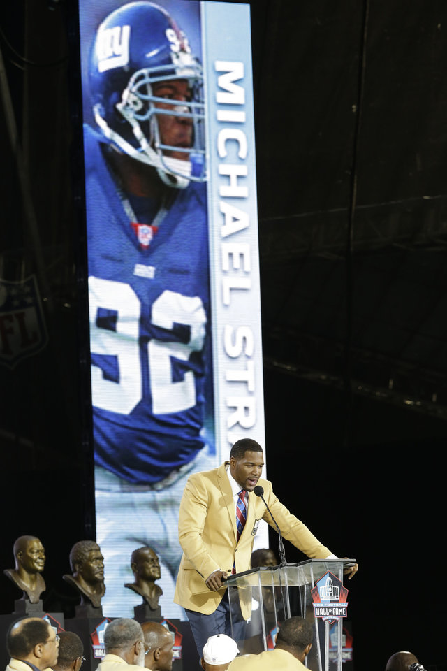 Photo - Hall of Fame inductee Michael Strahan speaks during the Pro Football Hall of Fame enshrinement ceremony at the Pro Football Hall of Fame on Saturday, Aug. 2, 2014, in Canton, Ohio. (AP Photo/Tony Dejak)
