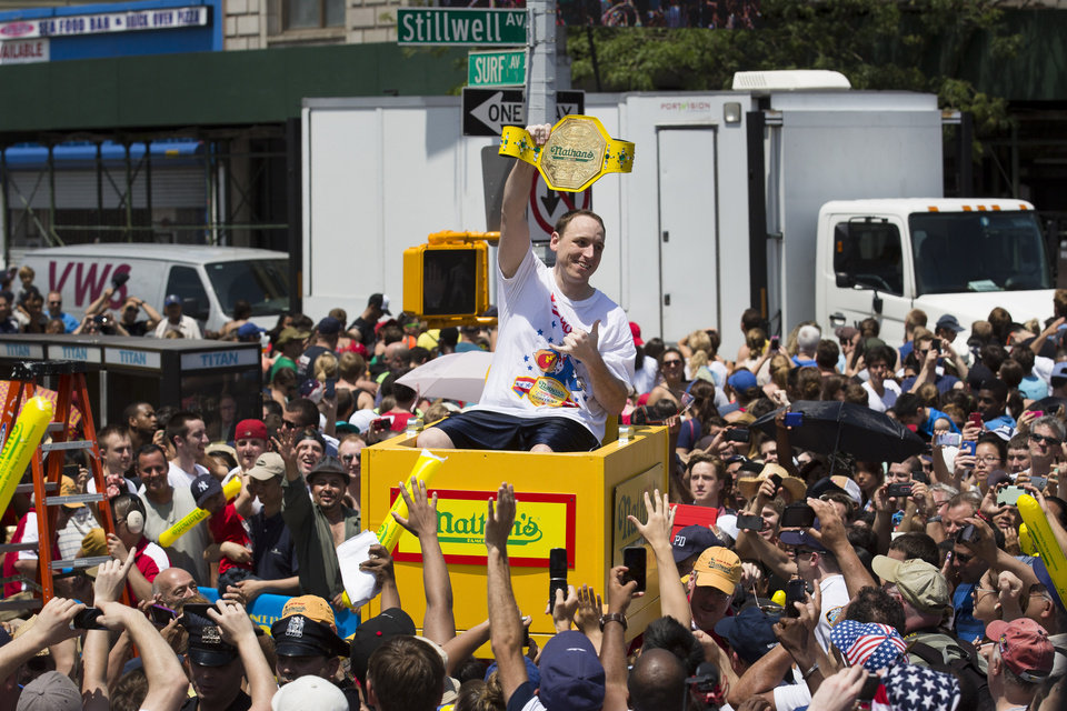 Joey Chestnut, six time winner of the Nathan's Famous Fourth of July International Hot Dog Eating contest, is carried to the competition stage through a crowd of fans, Thursday, July 4, 2013 at Coney Island, in the Brooklyn borough of New York. (AP Photo/John Minchillo)