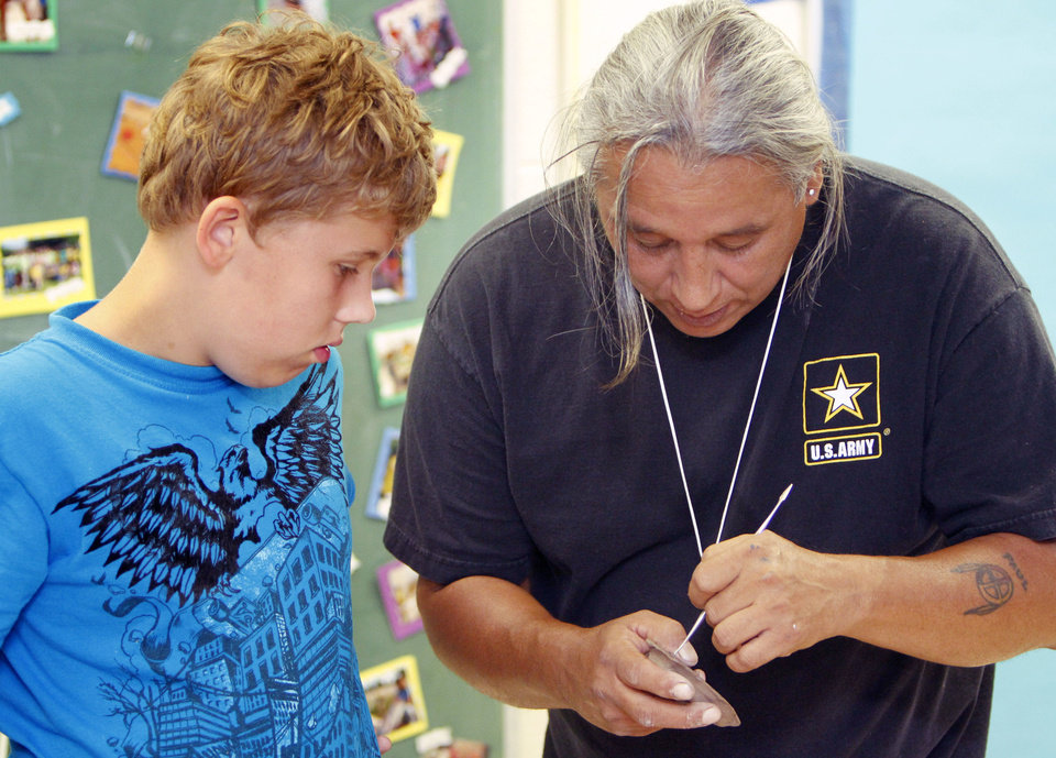 Photo - Albert Grayeagle helps Michael Shores, 10, create a clay flute Tuesday at Camp Chaverim, a summer camp sponsored by the Jewish Federation of Greater Oklahoma City.   PAUL HELLSTERN - Oklahoman