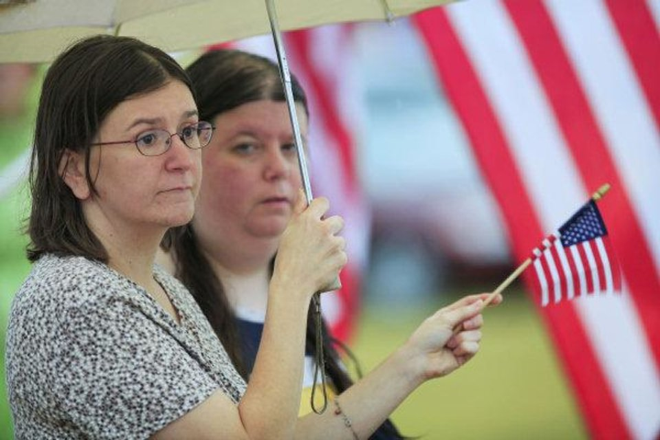 Photo - Amber Corum and Starla Cappello wave flags in support, beneath an umbrella, along I-35 during the funeral for 2nd Lt Jered Ewy, 33, of Edmond, at Henderson Hills Baptist Church.  David McDaniel - THE OKLAHOMAN