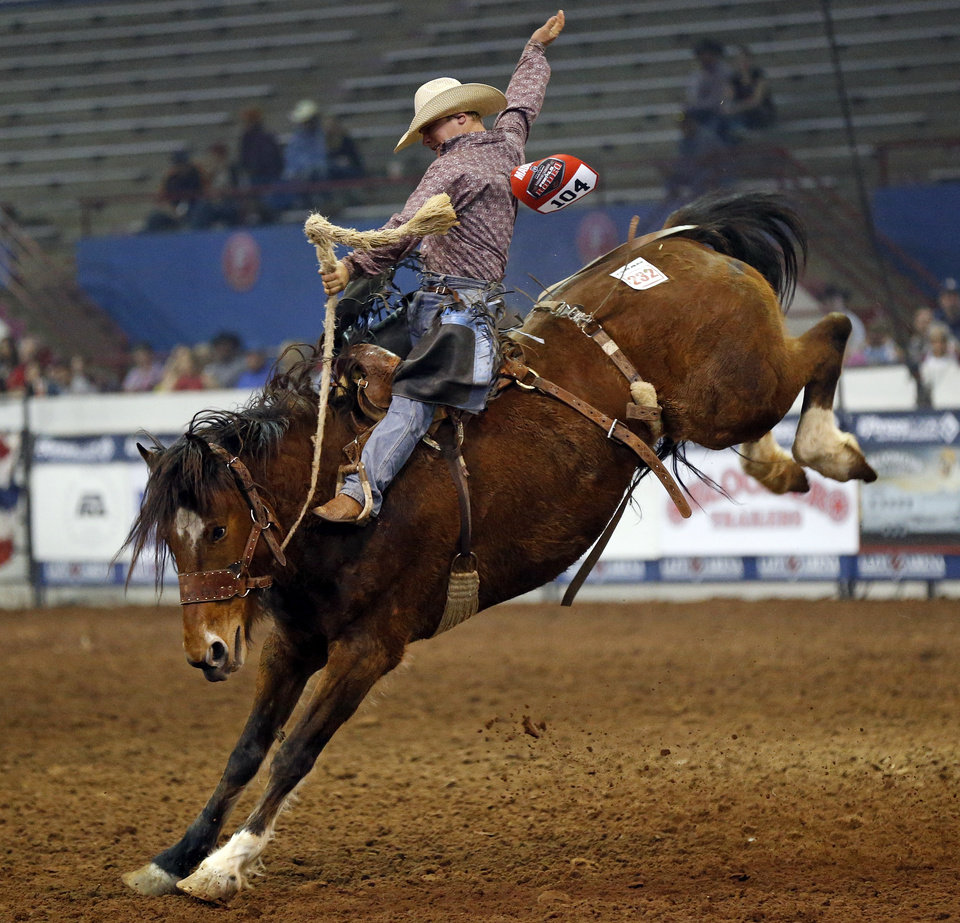 Photo - Casey Maddox of Wichita Falls, Texas, competes in saddle bronc riding during the National Circuit Finals Rodeo at the Lazy E Arena in Guthrie, Okla., Saturday afternoon, April 12, 2014. Photo by Nate Billings, The Oklahoman