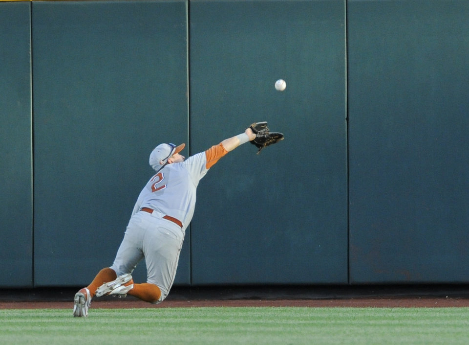 Photo - Texas center fielder Mark Payton (2) makes a leaping catch of a fly ball hit by UC Irvine's Taylor Sparks in the third inning of an NCAA baseball College World Series elimination game in Omaha, Neb., Wednesday, June 18, 2014. (AP Photo/Eric Francis)