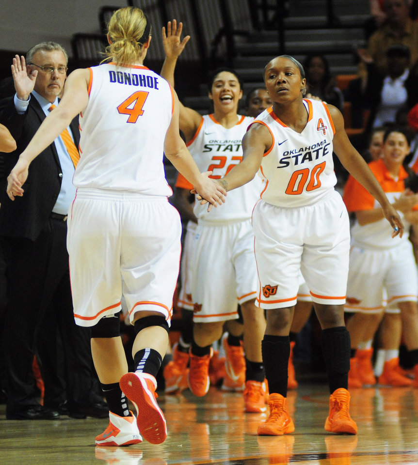 Oklahoma State guard Roshunda Johnson congratulates Cowgirl guard Liz Donohoe as Donohoe runs to the bench for a timeout during the Cowgirl's conference opener against West Virginia. West Virginia went on to defeat Oklahoma State 71-67 at Gallagher Iba Arena in Stillwater on Jan. 4, 2014.   Photo by KT King/For the Oklahoman