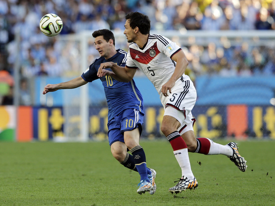 Photo - Argentina's Lionel Messi, left, battles for the ball with Germany's Mats Hummels during the World Cup final soccer match between Germany and Argentina at the Maracana Stadium in Rio de Janeiro, Brazil, Sunday, July 13, 2014. (AP Photo/Matthias Schrader)