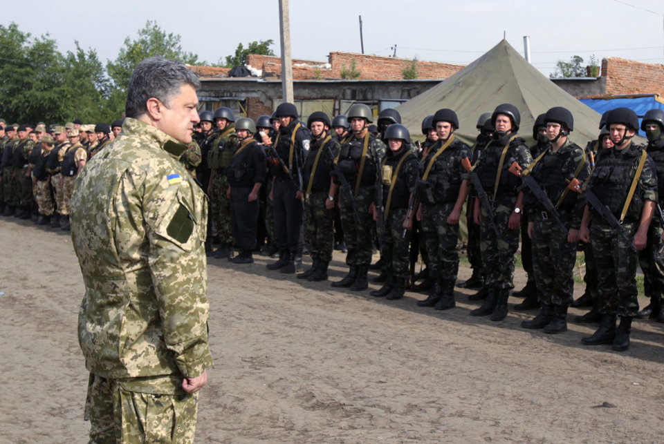 Photo - In this photo taken on Friday, June  20, 2014  in Izyum close to Slovyansk, eastern Ukraine, Ukrainian President Petro Poroshenko visits troops. Poroshenko in a televised address early Tuesday, July 1, 2014, said he was abandoning a unilateral cease-fire in the conflict with pro-Russian separatists and sending military forces back on the offensive after talks with Russia and European leaders failed to start a broader peace process. The cease-fire expired at 10 p.m. Monday.(AP Photo/Mykhailo Markiv, Pool)