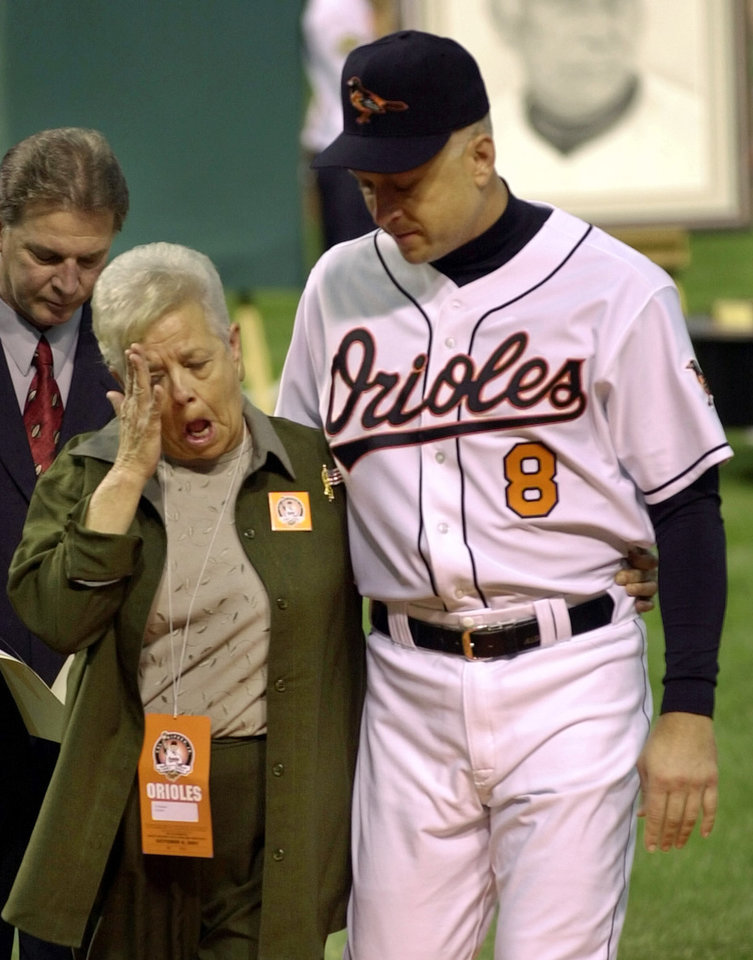 FILE - In this Oct. 6, 2001 file photo, Vi Ripken, mother of Cal Ripken of the Baltimore Orioles, wipes her eye while being escorted by her son after throwing out the ceremonial first pitch before Cal's final game, Saturday, Oct. 6, 2001, at Oriole Park at Camden Yards in Baltimore. Hall of Fame infielder Cal Ripken Jr. will talk publicly about the abduction of his mother. (AP Photo/Nick Wass)