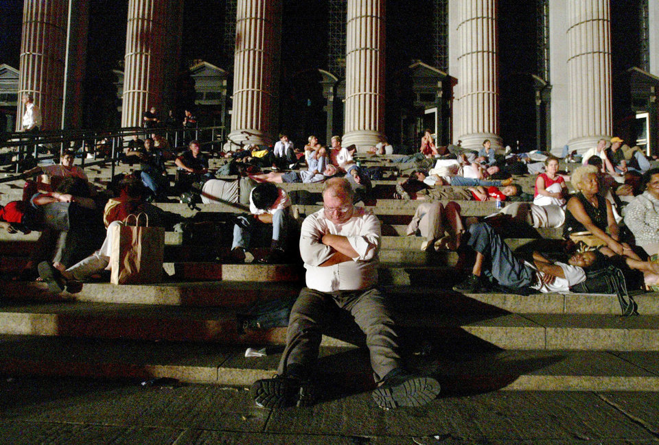 Photo - In this 2003 file photo, commuters sleep on the steps of the Central Post Office in New York after being stranded following a massive electrical blackout. About 50 million people lost power Aug. 14, 2003, when a tree branch touching high-power transmission lines in Ohio started an outage that cascaded across a broad swath from Michigan to New England and Quebec.  MIKE APPLETON - ASSOCIATED PRESS