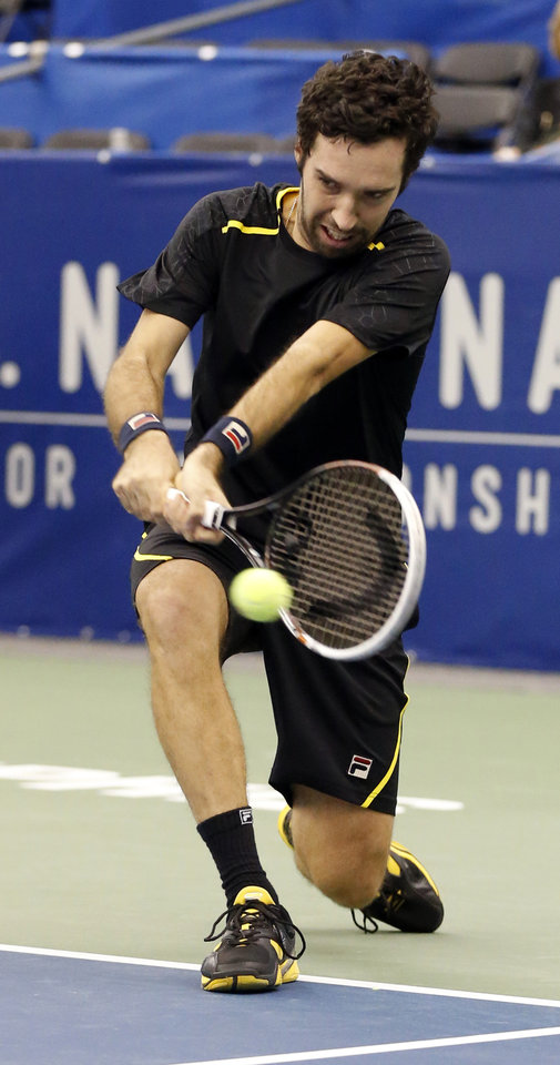 Photo - Mikhail Kukushkin, of Kazakhstan, hits a low return to Alex Kuznetsov during the second round match at the U.S. National Indoor Tennis  Championships on Thursday, Feb. 13, 2014, in Memphis, Tenn. (AP Photo/Rogelio V. Solis)