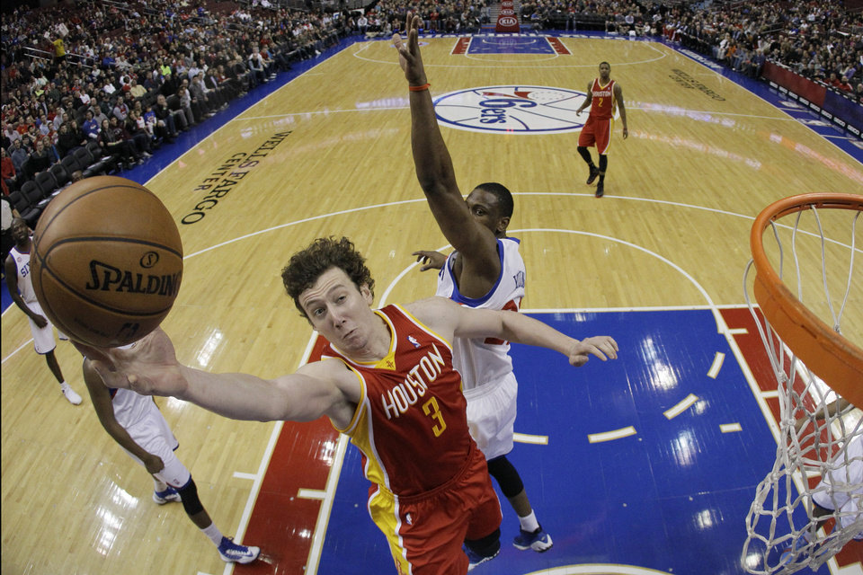 Photo - Houston Rockets' Omer Asik, left, of Turkey, goes up for a shot against Philadelphia 76ers' Thaddeus Young in the first half of an NBA basketball game, Saturday, Jan. 12, 2013, in Philadelphia. (AP Photo/Matt Slocum)