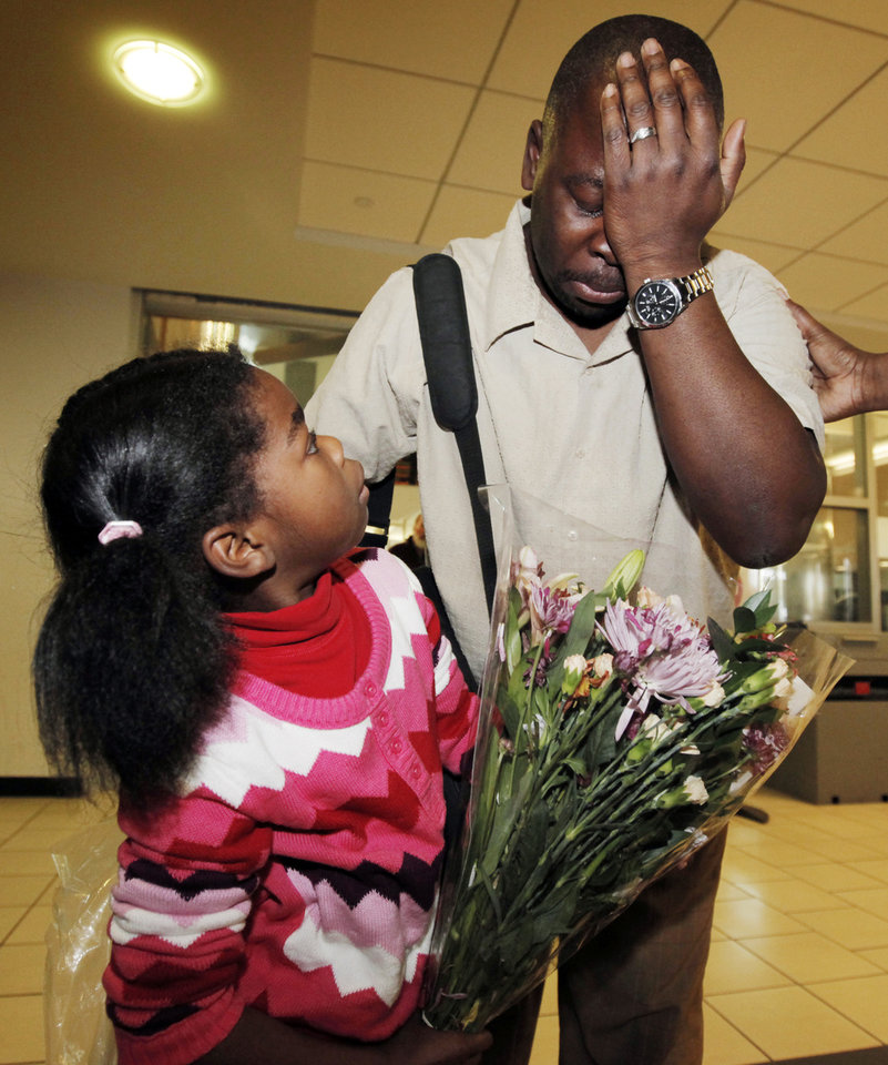 Photo - Humphreys Munai, right, is overcome with emotion while greeting his family, including daughter Imani Munai, 5, after arriving at Will Rogers World Airport in Oklahoma City, Thursday, January 14, 2010. Humphreys Munai was returning from Haiti where he was working for World Neighbors when the recent earthquake devastated the country. Photo by Nate Billings, The Oklahoman