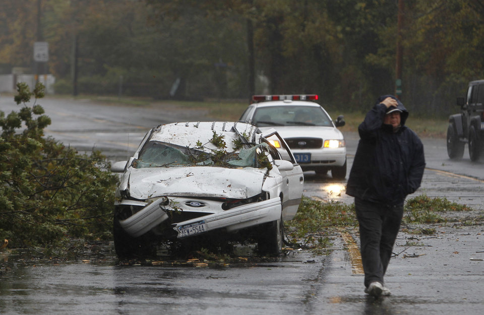 Photo -   A car crushed by a fallen tree sits along Montauk Highway as Hurricane Sandy approaches, Monday, Oct. 29, 2012, in Bay Shore, N.Y. Hurricane Sandy continued on its path Monday, forcing the shutdown of mass transit, schools and financial markets, sending coastal residents fleeing, and threatening a dangerous mix of high winds and soaking rain. (AP Photo/Jason DeCrow)