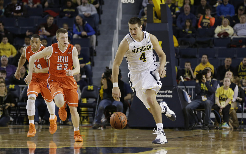 Photo - Michigan forward Mitch McGary (4) drives the ball up court during the first half of an NCAA college basketball game against Houston Baptist in Ann Arbor, Mich., Saturday, Dec. 7, 2013. (AP Photo/Carlos Osorio)