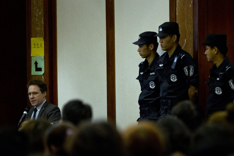 Photo - Policemen guard their positions near a translator, left, during a meeting between Malaysian officials and relatives of Chinese passengers onboard the missing Malaysia Airlines Flight 370 at a hotel in Beijing, China, Wednesday, April 30, 2014. The Australian agency heading up the search for the missing Malaysian jet has dismissed a claim by a resource survey company that it found possible plane wreckage in the northern Bay of Bengal.  (AP Photo/Alexander F. Yuan)
