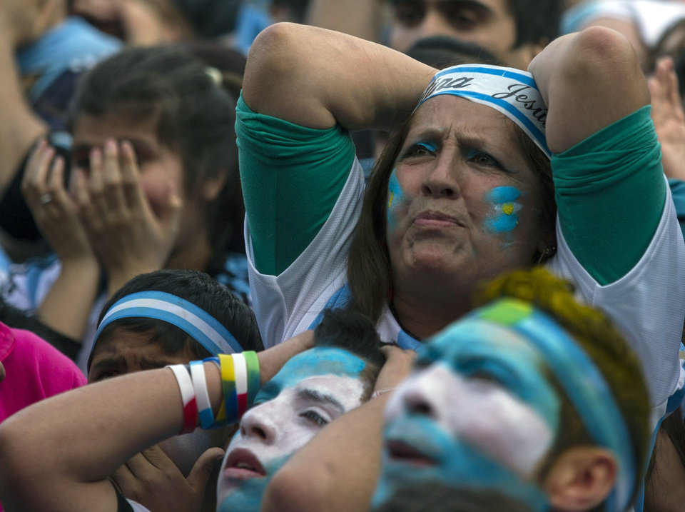 Photo - Argentina soccer fans react as they watch a live broadcast of the World Cup final match between Argentina and Germany on an outdoor television screen in Buenos Aires, Argentina, Sunday, July 13, 2014. Mario Goetze volleyed in the winning goal in extra time to give Germany its fourth World Cup title with a 1-0 victory over Argentina. (AP Photo/Ivan Fernandez)