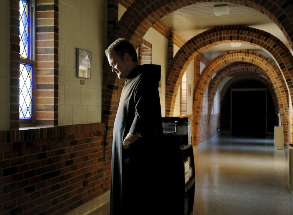 Photo -  The Rev. Simeon Spitz, a Benedictine monk, pauses in a hallway between the church and the kitchen in the monk's residence at St. Gregory's Abbey in Shawnee. He pushes a cart loaded with empty jars and containers of blackberries to the kitchen where he makes his jam. Photo by Jim Beckel, The Oklahoman   Jim Beckel