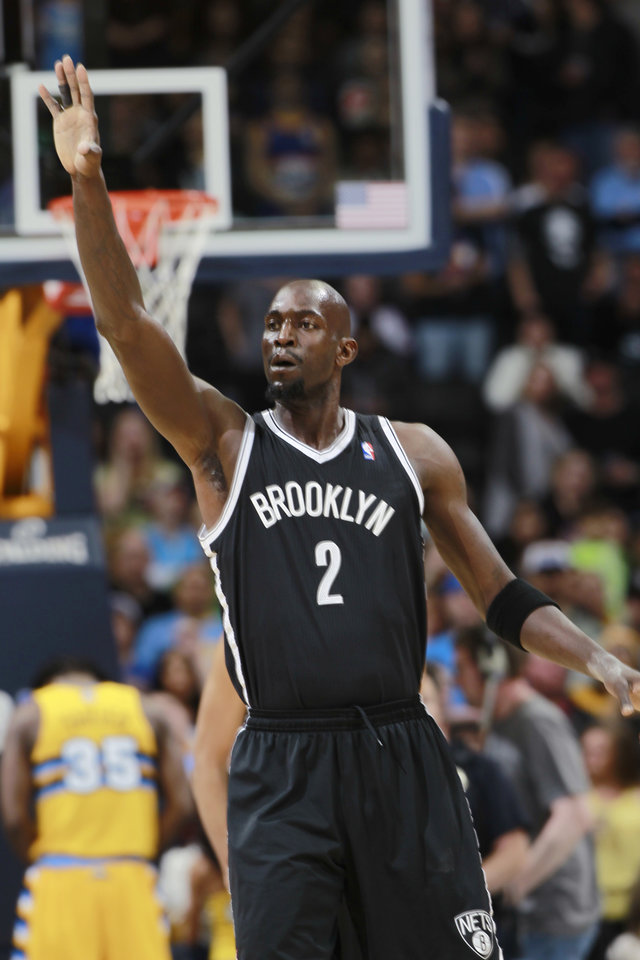 Photo - Brooklyn Nets forward Kevin Garnett congratulates a teammate for a basket against the Denver Nuggets in the first quarter of an NBA basketball game in Denver on Thursday, Feb. 27, 2014. (AP Photo/David Zalubowski)