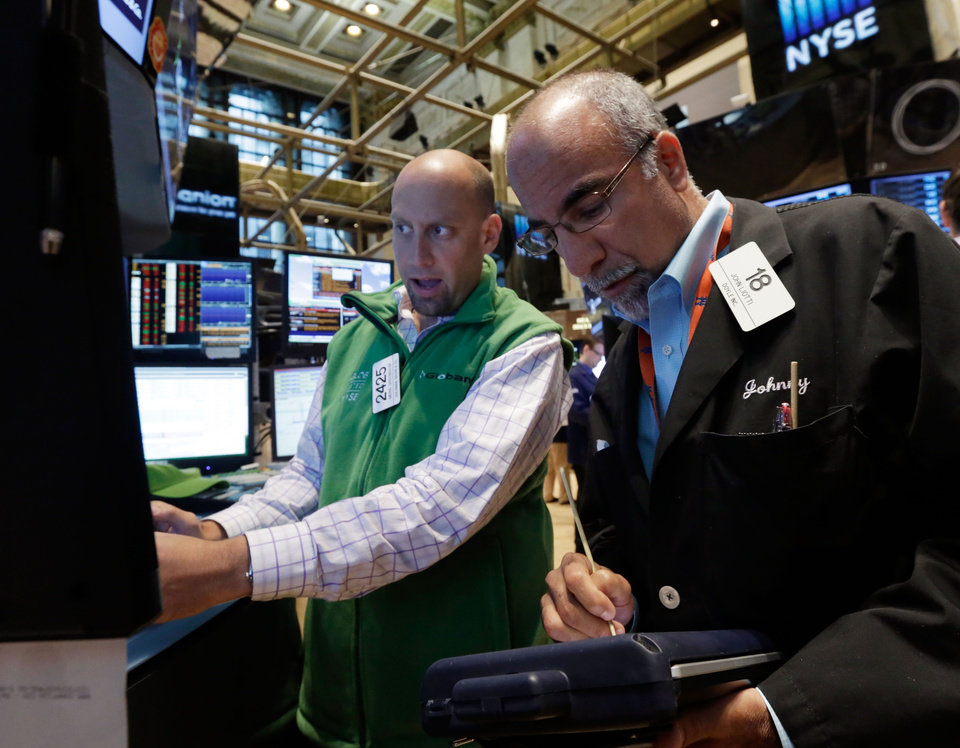 Photo - Specialist Meric Greenbaum, left, and trader John Liotti work on the floor of the New York Stock Exchange Friday, July 18, 2014. U.S. stocks are opening higher after Google, Honeywell and other big companies report their quarterly results. (AP Photo/Richard Drew)