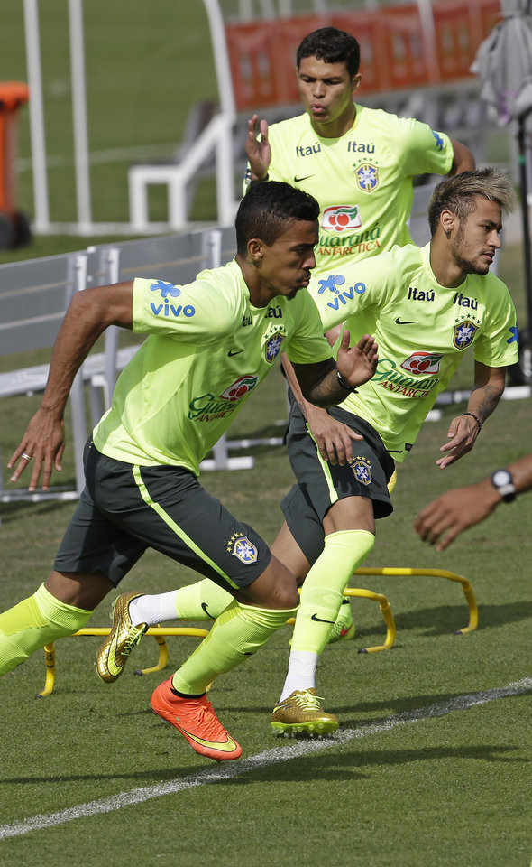 Photo - Brazil's Luiz Gustavo, left, Neymar, right, and Thiago Silva, back right, exercise during a training session at the Granja Comary training center in Teresopolis, Brazil, Thursday, June 26, 2014. Brazil will face Chile in their next World Cup soccer match, Saturday. (AP Photo/Andre Penner)
