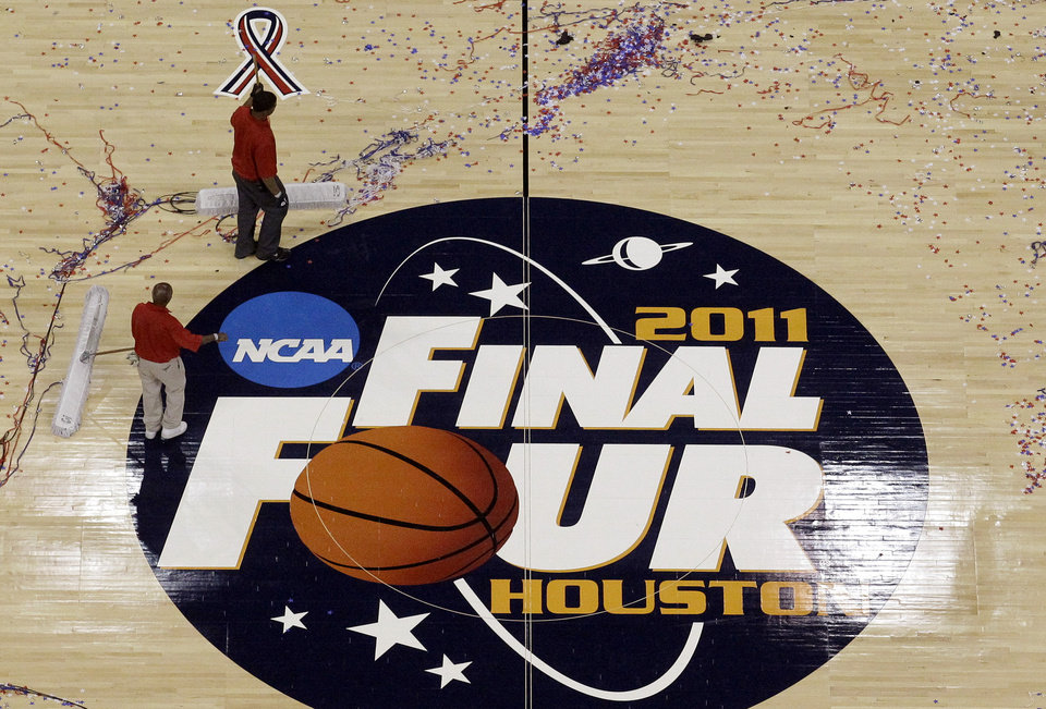 Photo - FILE - In this April 4, 2011, file photo, workers sweep confetti off the court following the men's NCAA Final Four college basketball championship game between Butler and Connecticut in Houston. Barely a month ago, the NCAA was shamed into apologizing for trying to rig its own investigation into funny business at the University of Miami. According to a new report, that apology didn't go nearly far enough. (AP Photo/David J. Phillip, File)