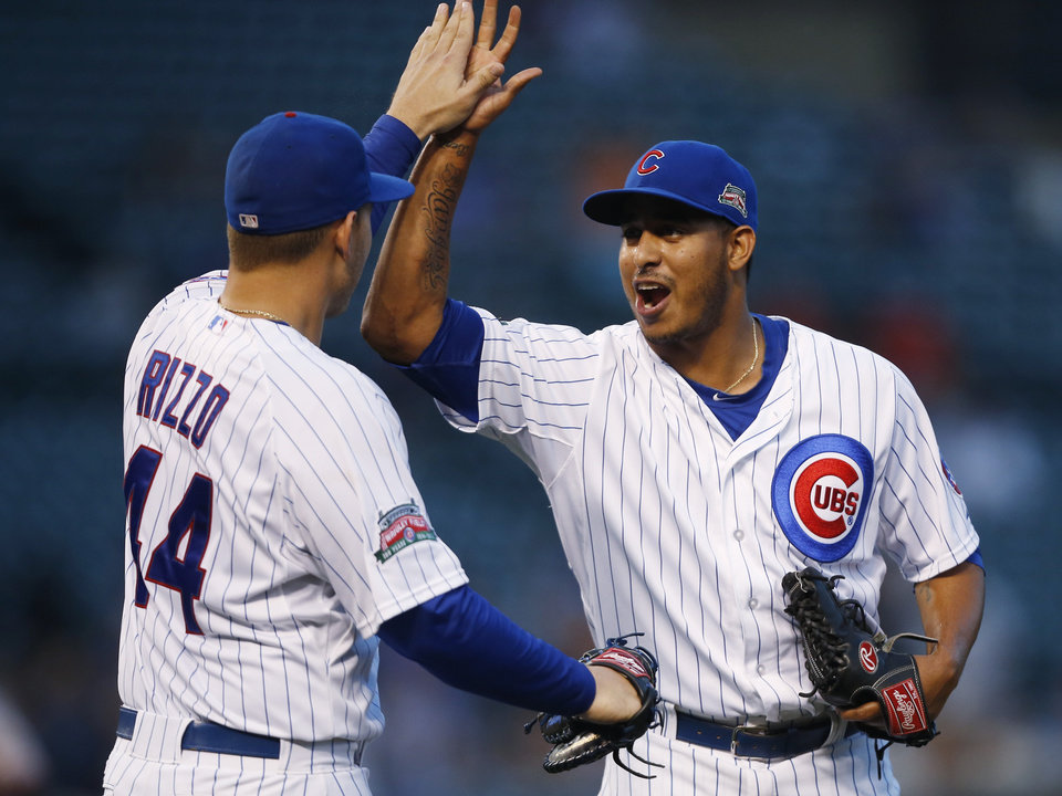 Photo - Chicago Cubs first baseman Anthony Rizzo, left, and relief pitcher Hector Rondon celebrate defeating the San Francisco Giants in a continuation of a rain-suspended baseball game that began Tuesday, on Thursday, Aug. 21, 2014, in Chicago. The Chicago Cubs won 2-1. (AP Photo/Andrew A. Nelles)