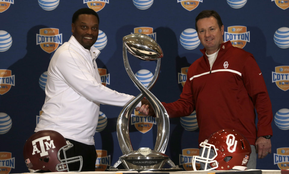 Photo - Texas A&M head coach Kevin Sumlin, left, and Oklahoma head coach Bob Stoops pose for photographers with the Cotton Bowl trophy after a news conference leading up to the NCAA college football game Wednesday, Jan. 2, 2013, in Irving, Texas. Before Sumlin became a successful head coach, he was on Stoops' staff at Oklahoma. Before that, they were both assistant coaches recruiting the same area. Now Sumlin takes his Texas A&M team against Stoops' Sooners in a Jan. 4th Cotton Bowl matchup of former Big 12 rivals that are both 10-2. (AP Photo/LM Otero) ORG XMIT: TXMO110