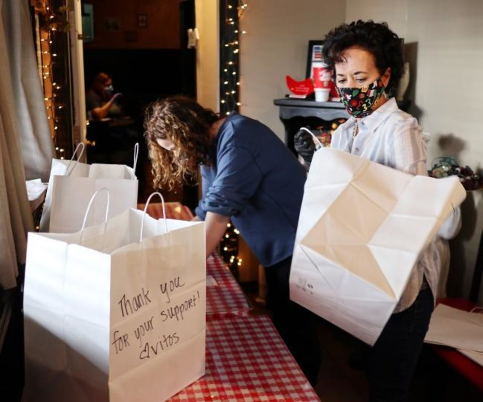 Photo -  Owner Cathy Cummings sorts orders for pickup May 13. Vito's Ristorante will continue to have carry out even after the dining room opens because of the limits in the number of customers allowed to dine in at once.  [Doug Hoke/The Oklahoman]