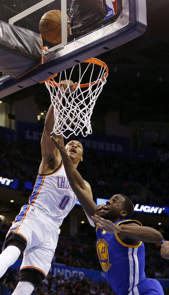 Photo - Oklahoma City's Russell Westbrook (0) misses a dunk against Golden State's Draymond Green (23) but the ball bounces up and falls through the basket in the second quarter during an NBA basketball game between the Golden State Warriors and the Oklahoma City Thunder at Chesapeake Energy Arena in Oklahoma City, Friday, Jan. 16, 2015. Photo by Nate Billings, The Oklahoman