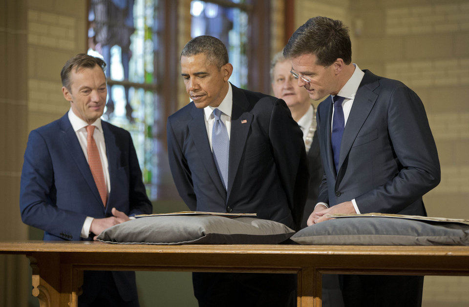 Photo - U.S. President Barack Obama, center, views the Act of Abjuration, widely considered to be the source document for the U.S. Declaration of Independence, during a tour of the Rijksmuseum with Museum Director Wim Pijbes, left, Prime Minister of the Netherlands Mark Rutte, right, and Mayor of Amsterdam Eberhard van der Laan, in Amsterdam, Netherlands, Monday, March 24, 2014. Obama is in the Netherlands for the Nuclear Security Summit. Obama also viewed the first trade and friendship agreement to be signed between the Netherlands and the USA in 1782, as well as other documents in the Rijksmuseum collection. (AP Photo/Pablo Martinez Monsivais)