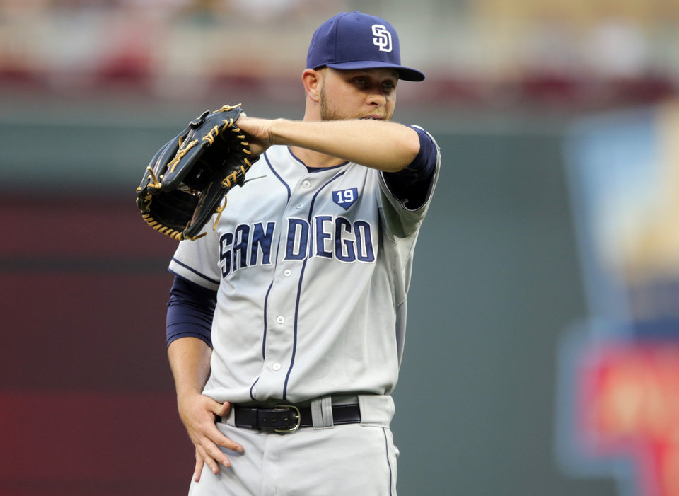 Photo - San Diego Padres pitcher Jesse Hahn wipes his chin as he gave up a walk to Minnesota Twins' Trevor Plouffe  in the first inning of a baseball game, Tuesday, Aug. 5, 2014, in Minneapolis. (AP Photo/Jim Mone)