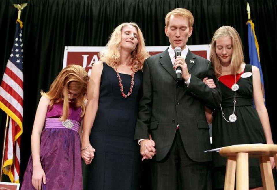 Photo - James Lankford, together with his daughters Jordan, left, and Hannah  and his wife, Cindy, prays with supporters during a watch party at the Oklahoma Sports Hall of Fame in Oklahoma City on Aug.   John Clanton - The Oklahoman