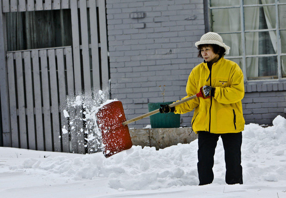 Photo - A resident on Britton Road shovels snow off the driveway on Thursday, Feb. 3, 2011, Oklahoma City, Okla.   Photo by Chris Landsberger, The Oklahoman