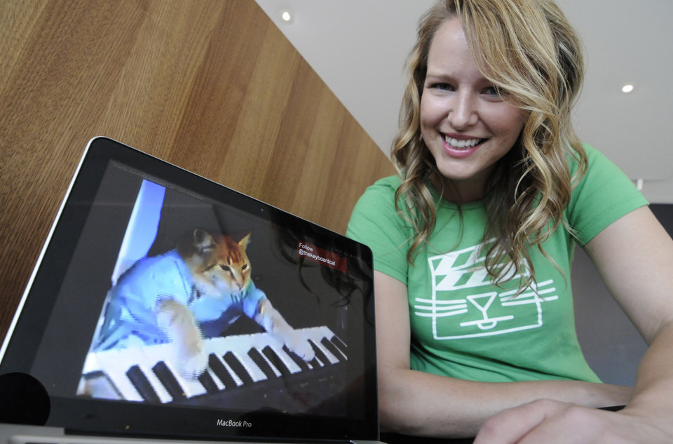 "FILE - In this Wed., Aug. 29, 2012 file photo, Katie Hill, a program associate with the Walker Art Center, shows a frame from a cat video of a cat playing the piano, in Minneapolis. The Walker presented its  first ""Internet Cat Video Film Festival"" to showcase the best in filmed feline hijinks that drew a crowd of more than 10,000 people. 80 videos culled from 10,000 submissions that covered the simple, funny moment to polished animations and kitty works made by trained filmmakers were shown to the public for free. (AP Photo/Jim Mone, File)"