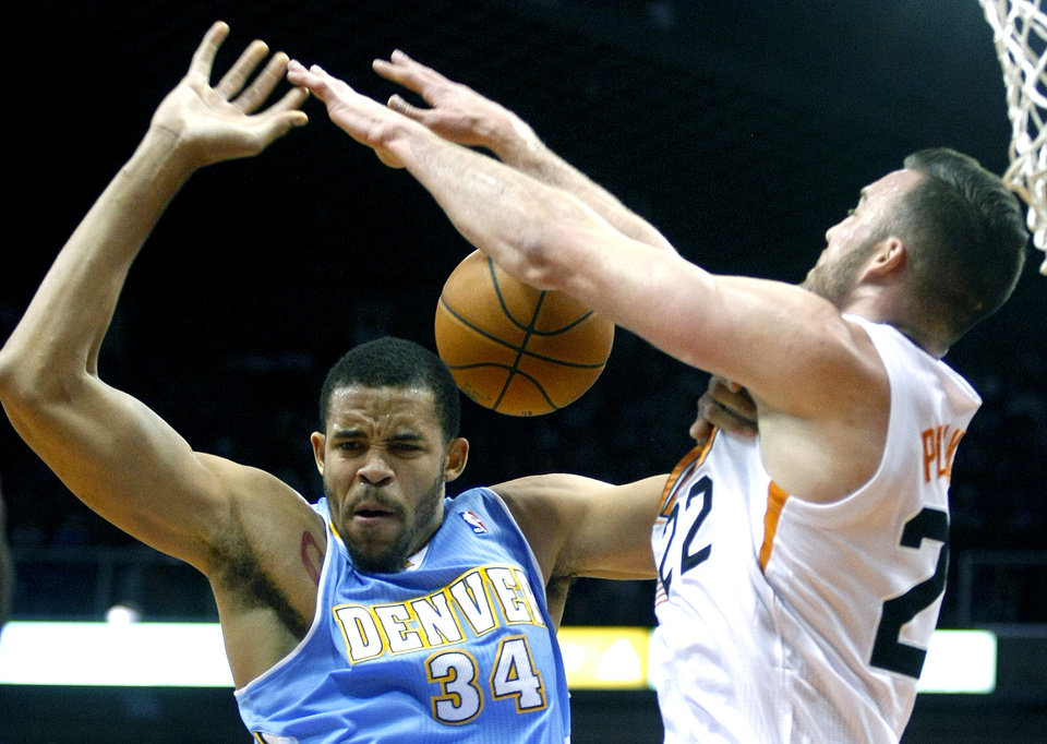 Photo - Denver Nuggets center JaVale McGee (34), left, is fouled by Phoenix Suns center Miles Plumlee (22) in the first quarter during an NBA basketball game on Friday, Nov. 8, 2013, in Phoenix. (AP Photo/Rick Scuteri)
