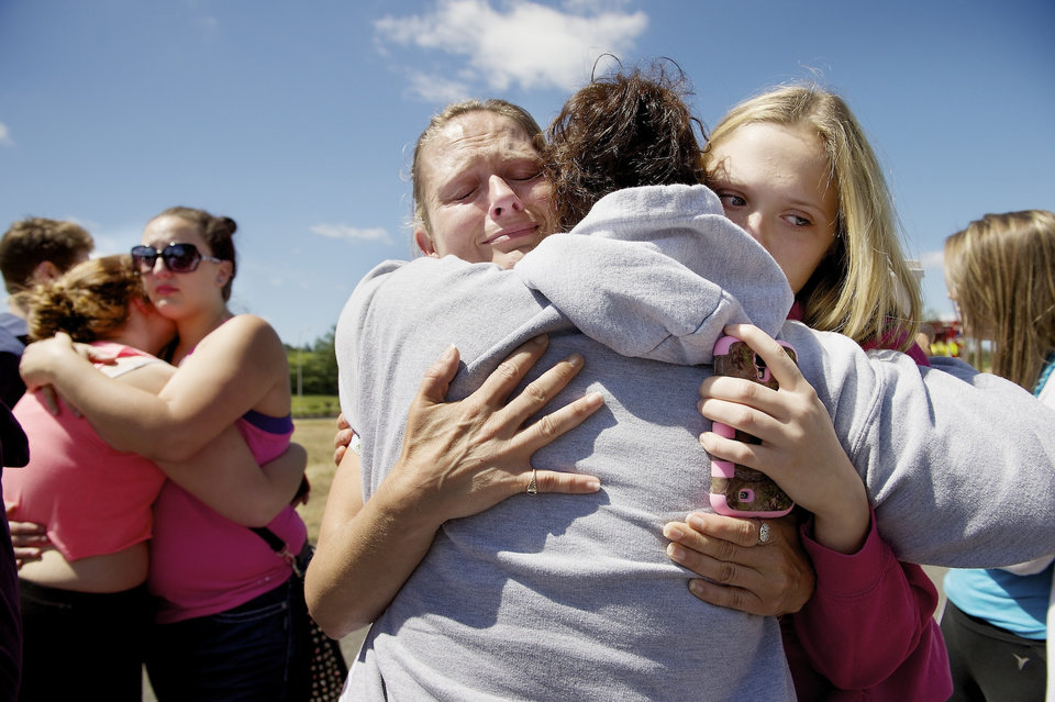 Photo - Brandi Wilson, left, and her daughter, Trisha Wilson, 15, right, embrace Trish Hall, a mother waiting for her student, as students arrived at the Fred Meyer grocery store parking lot in Wood Village, Ore., after a shooting at Reynolds High School Tuesday, June 10, 2014, in nearby Troutdale. A gunman killed a student at the high school east of Portland Tuesday and the shooter is also dead, police said. (AP Photo/Troy Wayrynen)