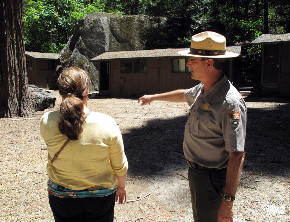 Photo -   In this on Tuesday, June 12, 2012 photo, park spokesman Scott Gediman, right, speaks with Lisa Cesaro of the Delaware North Company, which operates the lodging and other concessions at Yosemite National Park. This portion of the family friendly Curry Village sits in an area that a new study says is at high risk of catastrophic rock falls. It was built in 1899 at the base of Glacier Point amid boulders from previous rock falls. One-third of the village's 600 cabins have been closed since a rock fall in 2008, and the study says a dozen others and several employee dormitories also must close. (AP Photo/Tracie Cone)