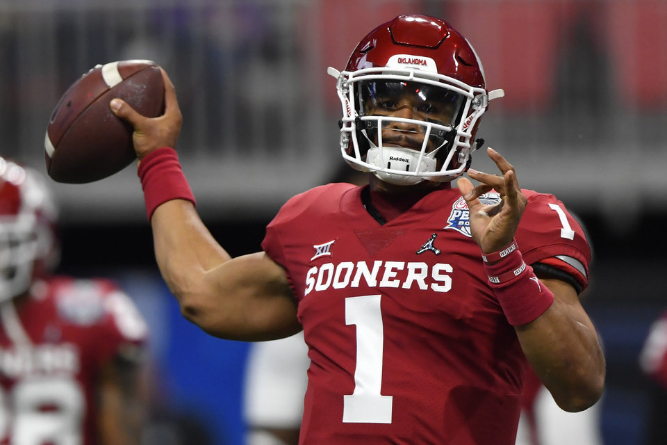 Photo - Oklahoma quarterback Jalen Hurts (1) warms up before the first half of the Peach Bowl NCAA semifinal college football playoff game against LSU, Saturday, Dec. 28, 2019, in Atlanta. (AP Photo/John Amis)