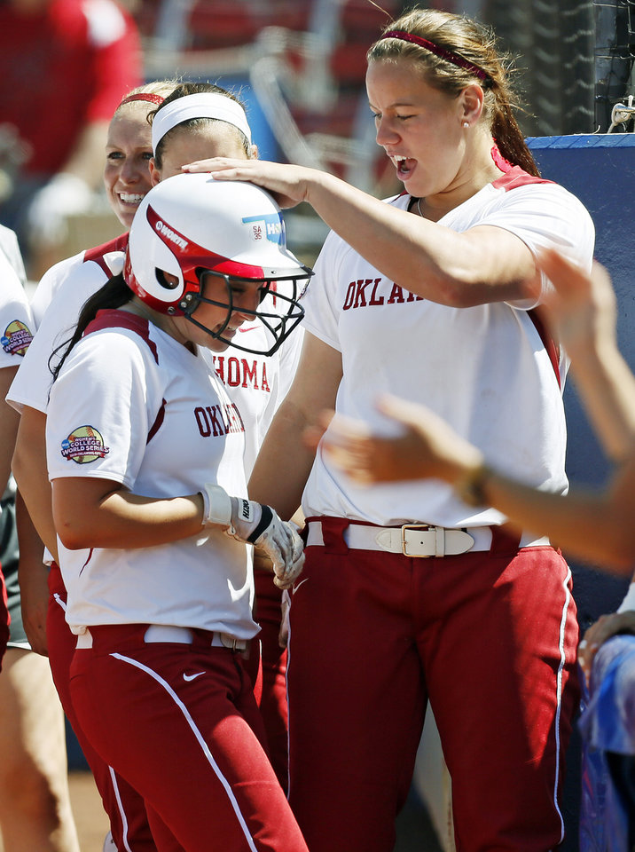 Photo - OU pitcher Keilani Ricketts (10) pats Erin Miller (48) on the helmet after Miller scored in the fourth inning during an NCAA softball game in the Women's College World Series between Oklahoma and Texas at ASA Hall of Fame Stadium in Oklahoma City, Saturday, June 1, 2013. Oklahoma won 10-2 in five innings. Photo by Nate Billings, The Oklahoman