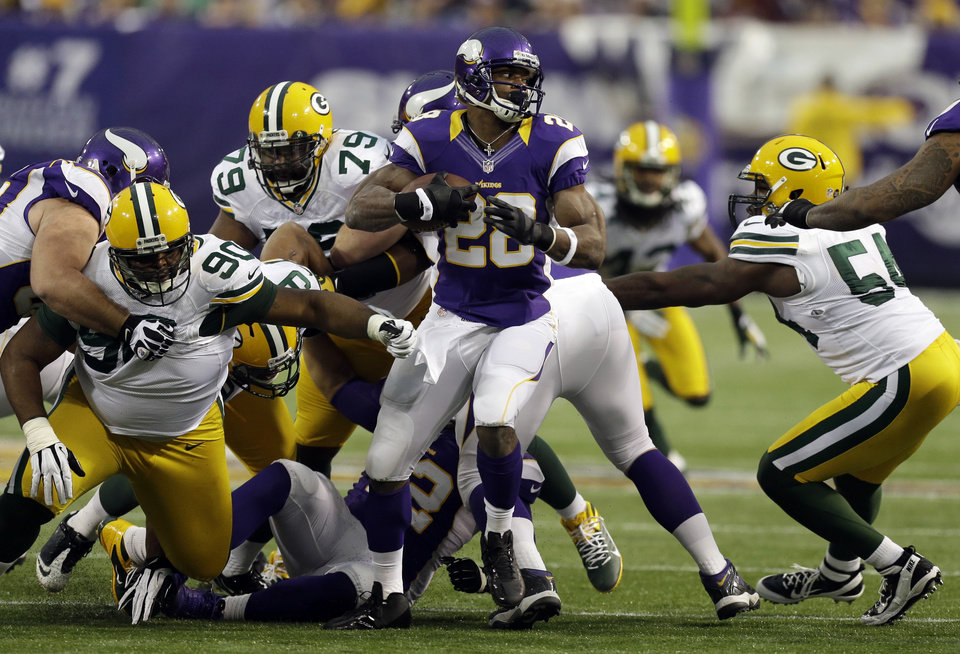Photo - Minnesota Vikings running back Adrian Peterson, center, runs from Green Bay Packers defenders B.J. Raji (90), Ryan Pickett and Dezman Moses, right, during the first half of an NFL football game Sunday, Dec. 30, 2012, in Minneapolis. (AP Photo/Charlie Neibergall)
