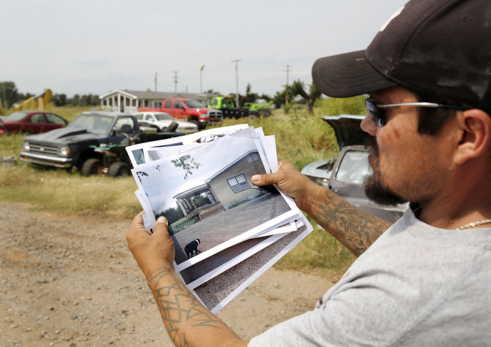 Photo - Jeremy Knox shows photos of  his Carney home/business as they looked before being destroyed in the May 19 tornado. Knox also is on the temporary high risk pool for health insurance due to a serious pre-existing health condition.  Photo  by Jim Beckel, The Oklahoman.