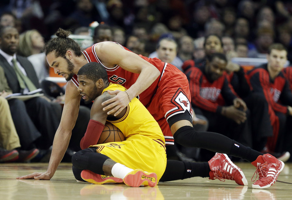 Photo - Cleveland Cavaliers' Kyrie Irving, bottom, recovers a loose ball against Chicago Bulls' Joakim Noah in the first quarter of an NBA basketball game Wednesday, Jan. 22, 2014, in Cleveland. (AP Photo/Mark Duncan)