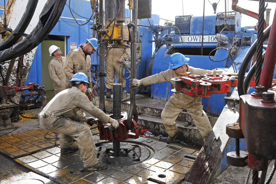 Photo - Floorman Justin Stanfill, Paul Tabarez and William Reed break a joint in drill pipe is pulled on a SandRidge oil drilling rig near Medford, Thursday, October 18, 2012. In back is Rig Manager Gordon Frayne in the white hat. This is for Oklahoma Inc. Photo By David McDaniel/The Oklahoman